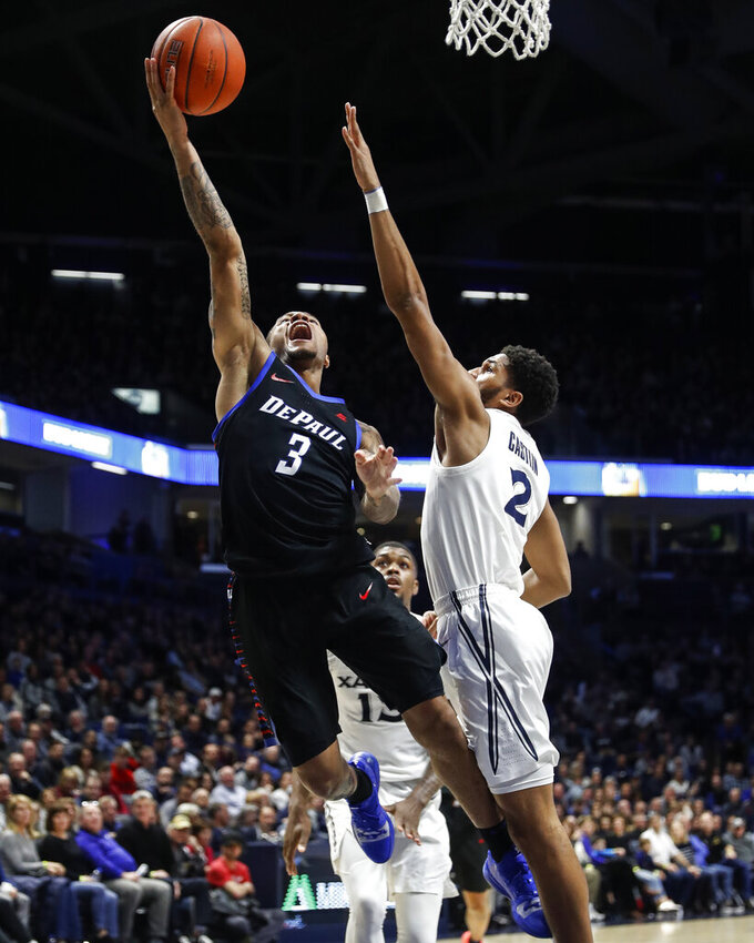 DePaul's Devin Gage (3) shoots against Xavier's Kyle Castlin (2) during the second half of an NCAA college basketball game, Saturday, Feb. 9, 2019, in Cincinnati. (AP Photo/John Minchillo)