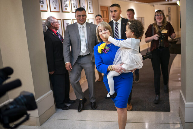 New Mexico Gov. Michelle Lujan Grisham is silenced by her granddaughter Avery Stewart while being escorted out following the State of the State address opening the New Mexico legislative session in the house chambers at the state Capitol in Santa Fe, N.M. on Tuesday, Jan. 21, 2020. (AP Photo/Craig Fritz)
