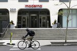 A bicyclists pedals past an entrance to a Moderna, Inc., building, Monday, May 18, 2020, in Cambridge, Mass. Moderna announced Monday that an experimental vaccine against the coronavirus showed encouraging results in very early testing, triggering hoped-for immune responses in eight healthy, middle-aged volunteers.(AP Photo/Bill Sikes)
