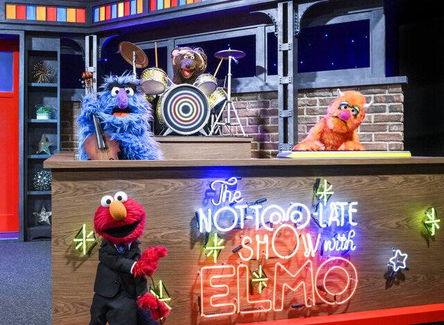 "This image released by Sesame Workshop shows muppet character Elmo, bottom left, who will host a family friendly show called ""The Not Too Late Show with Elmo."" It begins streaming May 27 on HBO Max. (Zach Hyman/Sesame Workshop via AP)"