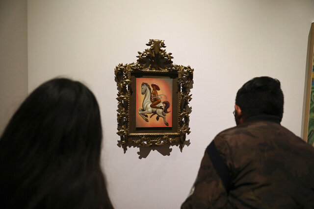 People watch a painting showing 1910-17 Mexican revolutionary hero Emiliano Zapata nude, wearing high heels and a pink, broad-brimmed hat, straddling a horse, in Mexico City, Tuesday, Dec. 10, 2019. The work by Fabian Chairez is part of an exhibit about Zapata in one of Mexico City's premiere arts venues, the Fine Arts Palace. (AP Photo/Eduardo Verdugo)