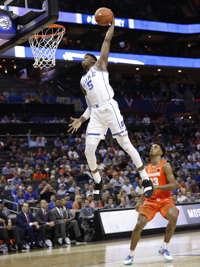 Duke's RJ Barrett (5) goes up to dunk against Syracuse's Frank Howard (23) during the second half of an NCAA college basketball game in the Atlantic Coast Conference tournament in Charlotte, N.C., Thursday, March 14, 2019. (AP Photo/Chuck Burton)