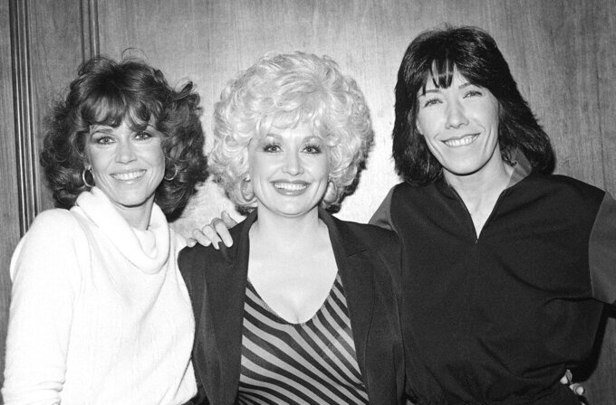 """FILE - Jane Fonda, from left, Dolly Parton and Lily Tomlin get together Dec. 12, 1980 at a Los Angeles news conference to promote their movie """"9 To 5"""". Parton's 1980's hit song """"9 to 5"""" has been flipped by Squarespace, the company that helps users build and host their own websites, for a Super Bowl commercial debuting Tuesday, Feb. 2, 2021. Oscar winner Damien Chazelle of """"La La Land"""" fame directed the spot. (AP Photo/Wally Fong, File)"""