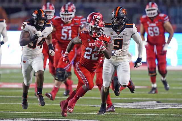 Utah running back Ty Jordan (22) carries the ball during the first half of the team's NCAA college football game against Oregon State on Saturday, Dec. 5, 2020, in Salt Lake City. (AP Photo/Rick Bowmer)