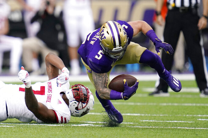 Washington's Sean McGrew (5) is tripped by Arkansas State's Anthony Switzer in the first half of an NCAA college football game, Saturday, Sept. 18, 2021, in Seattle. (AP Photo/Elaine Thompson)