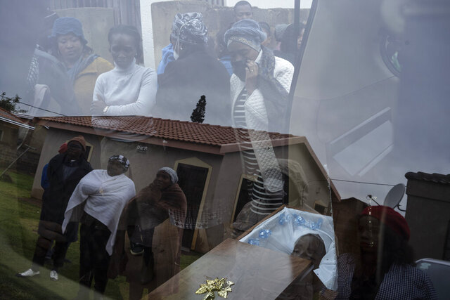 Mourners look at the body of 5-year-old Wandi Zitho at his funeral in Orange Farm, South Africa, on April 28, 2020. The boy was murdered in a suspected witchcraft ritual and his body was found in his neighbor's tavern. (AP Photo/Bram Janssen)