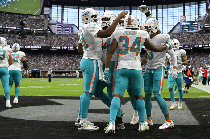 Miami Dolphins running back Malcolm Brown (34) celebrates after scoring a touchdown against the Las Vegas Raiders during the first half of an NFL football game, Sunday, Sept. 26, 2021, in Las Vegas. (AP Photo/David Becker)