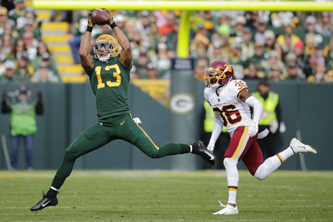 Green Bay Packers' Allen Lazard catches a pass in front of Washington Football Team's Danny Johnson during the first half of an NFL football game Sunday, Oct. 24, 2021, in Green Bay, Wis. (AP Photo/Aaron Gash)