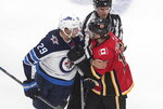 Winnipeg Jets' Patrik Laine (29) and Calgary Flames' Matthew Tkachuk (19) get in each other's face during the second period of an NHL hockey playoff game Saturday, Aug. 1, 2020 in Edmonton, Alberta. (Jason Franson/The Canadian Press via AP)