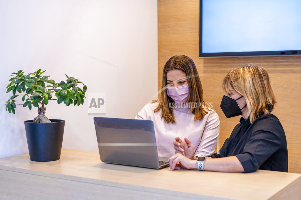 Female dentist and receptionist wearing protective face mask discussing over laptop at desk in clinic