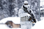 An armed Swiss police officer stands guard on the roof of the congress center where the annual meeting of the World Economic Forum, WEF, take place in in Davos, Monday, Jan. 21, 2019. (AP Photo/Markus Schreiber)