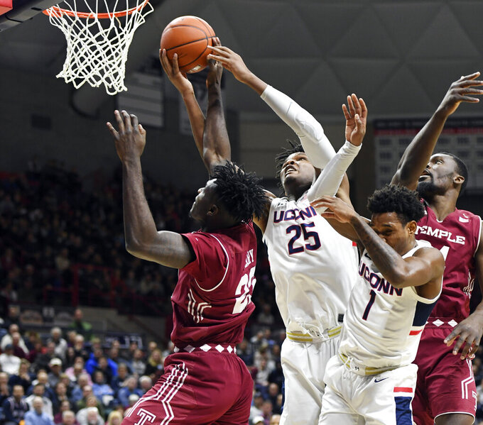 Temple's Tim Waddington (25) and Connecticut's Josh Carlton (25) battle for a rebound in the first half of an NCAA college basketball game Thursday, March 7, 2019, in Storrs, Conn. (AP Photo/Stephen Dunn)