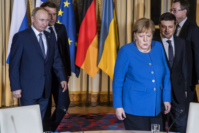 Russian President Vladimir Putin, left, French President Emmanuel Macron, second left, Ukrainian President Volodymyr Zelenskiy, right, and German Chancellor Angela Merkel arrive at a working session at the Elysee Palace Monday, Dec. 9, 2019 in Paris. Russian President Vladimir Putin and Ukraine's president are meeting for the first time at a summit in Paris to find a way to end the five years of fighting in eastern Ukraine. (Christophe Petit Tesson/Pool via AP)