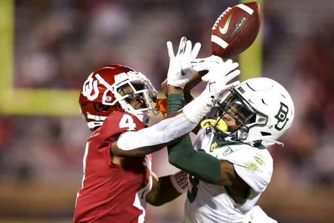 Oklahoma cornerback Jaden Davis (4) knocks away a pass intended for Baylor wide receiver Tyquan Thornton (9) during an NCAA college football game in Norman, Okla., Saturday, Dec. 5, 2020. (Ian Maule/Tulsa World via AP)