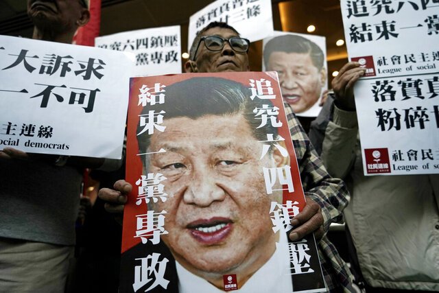 Pro-democracy activists hold up placards of Chinese President Xi Jinping at a ferry terminal in Hong Kong, Wednesday, Dec. 18, 2019. A ferry company barred a Hong Kong activist