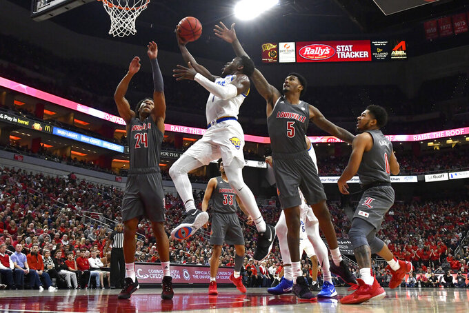 CORRECTS TO FIRST HALF NOT SECOND HALF - Pittsburgh guard Xavier Johnson (1) goes up for a layup between the defensive pressure of Louisville forwards Dwayne Sutton (24) and Malik Williams (5) during the fist half of an NCAA college basketball game in Louisville, Ky., Friday, Dec. 6, 2019. (AP Photo/Timothy D. Easley)