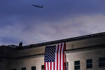 FILE - In this Friday, Sept. 11, 2020 file photo, a plane takes off from Washington Reagan National Airport as a large U.S. flag is unfurled at the Pentagon ahead of ceremonies at the National 9/11 Pentagon Memorial to honor the 184 people killed in the 2001 terrorist attack on the Pentagon, in Washington, Friday, Sept. 11, 2020. (AP Photo/J. Scott Applewhite, File)