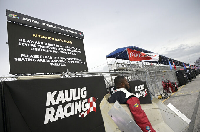 A team member carries a part from a pit stall during a weather delay of a NASCAR Xfinity Series auto race at Daytona International Speedway, Friday, Aug. 27, 2021, in Daytona Beach, Fla. (AP Photo/Phelan M. Ebenhack)