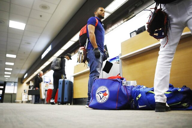Toronto Blue Jays minor league baseball player Steward Berroa, center, prepares to fly home along with his teammates from the Dominican Republic at the Tampa International Airport in Tampa, Florida on Sunday, March 15, 2020. Flight schedules for departures and arrivals remain normal during the coronavirus pandemic.(Octavio Jones/Tampa Bay Times via AP)