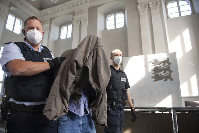 The accused in the trial of a six-time murder in Rot am See is led to his seat in a hall of the regional court in Ellwangen, Germany, Friday, July 10, 2020. The young man is said to have killed his parents, two half-brothers and sisters as well as his uncle and aunt at the end of January 2020. The public prosecutor accuses the German of murder and attempted murder. (Marijan Murat/dpa via AP)