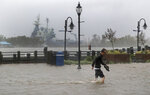 A man crosses a flooded street in downtown Wilmington, N.C., after Hurricane Florence made landfall Friday, Sept. 14, 2018. (AP Photo/Chuck Burton)