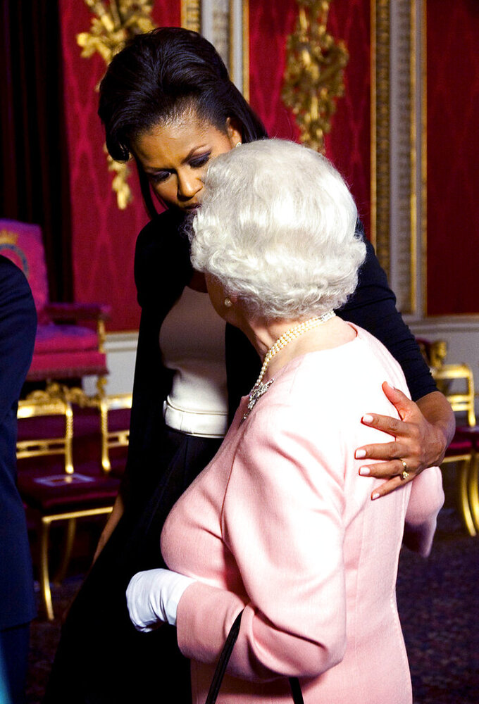 FILE - In this April 1, 2009 file photo, Michelle Obama, wife of U.S. President Barack Obama, left, walks with Queen Elizabeth II at the reception at Buckingham Palace in London. (Daniel Hambury/Pool Photo via AP, File)