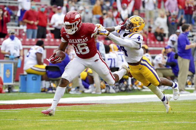Arkansas receiver Treylon Burks (16) shakes off LSU defender Todd Harris Jr. (4) as he runs for a touchdown during the first half of an NCAA college football game Saturday, Nov. 21, 2020, in Fayetteville, Ark. (AP Photo/Michael Woods)
