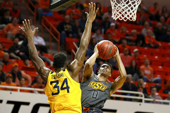 Oklahoma State guard Avery Anderson III (0) shoots as West Virginia forward Oscar Tshiebwe (34) defends in the first half of an NCAA college basketball game in Stillwater, Okla., Monday, Jan. 6, 2020. (AP Photo/Sue Ogrocki)