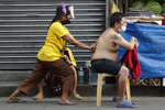 A man wearing a face mask to prevent the spread of the coronavirus gets a massage after attending Catholic mass in downtown Manila, Philippines. (AP Photo/Aaron Favila)