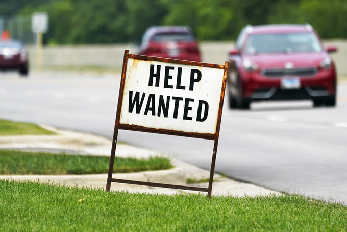 FILE - In this Tuesday, July 27, 2021, file photo, a help-wanted sign is displayed at a gas station in Mount Prospect, Ill. The gulf between record job openings and a lack of people taking those jobs is forcing Wall Street to reassess the pace of the economic recovery. (AP Photo/Nam Y. Huh, File)