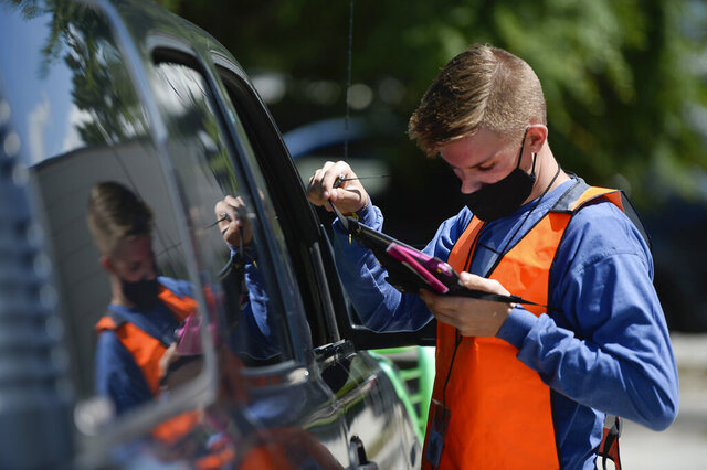 Poll worker Seth Ahlers checks on a voter's registration as people line up at one of 12 drive-up voting assistance centers in Salt Lake County, Utah, Tuesday, June 30, 2020, to get ballots to replace lost ones or get help for unaffiliated voters registering Republican to be able to vote in the primary. Utah was one of a handful of states that decided not to open any in-person polling places this year due to the coronavirus pandemic.(Francisco Kjolseth/The Salt Lake Tribune via AP)