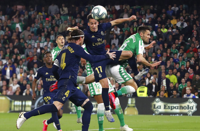 Real Madrid's Lucas Vazquez jumps for the ball against Betis' Alfonso Pedraza during La Liga soccer match between Betis and Real Madrid at the Benito Villamarin stadium in Seville, Spain, Sunday, March. 8, 2020. (AP Photo/Miguel Morenatti)