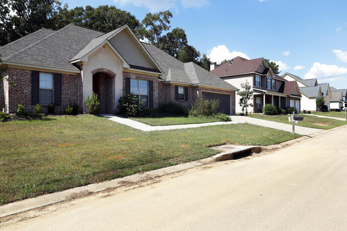 In this Sept. 25, 2019, photo houses in a Brandon, Miss., neighborhood are photographed. Many small companies tied to the housing market are seeing a slowdown in business, one that could continue into 2020. Reports on home sales, the remodeling market and sales of furniture and home furnishings show the spreading fallout from rising prices for houses and apartments. (AP Photo/Rogelio V. Solis)
