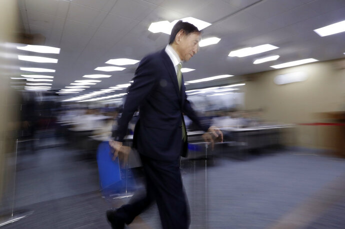 Bank of Korea Gov. Lee Ju-yeol arrives for a press conference in Seoul, South Korea, Thursday, July 12, 2018. South Korea's central bank has cut its forecast on the country's economy, citing mounting uncertainties from the U.S.-China trade battle. Bank of Korea said Thursday it lowered its growth outlook on Asia's fourth-largest economy to 2.9 percent this year, compared with its earlier forecast of 3 percent growth.(AP Photo/Lee Jin-man)