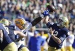 Notre Dame quarterback Ian Book (12) throws in interception as he is hit by Pittsburgh defensive lineman Jaylen Twyman during the second half of an NCAA college football game, Saturday, Oct. 13, 2018, in South Bend, Ind. Notre Dame won 19-14. (AP Photo/Darron Cummings)