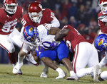 FILE - In this Saturday, Nov. 17, 2018, file photo, Kansas running back Khalil Herbert, center, is tackled by Oklahoma defensive lineman Kenneth Mann, right, and Oklahoma linebacker Curtis Bolton, left, during the second half of an NCAA college football game in Norman, Okla. Oklahoma's poor performances on defense have nearly torpedoed one of the best offenses in college football history. (AP Photo/Alonzo Adams, File)