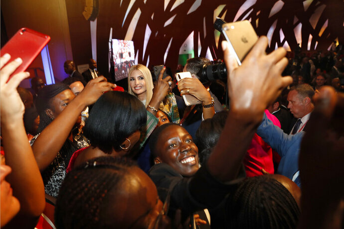 People crowd around U.S. White House senior adviser Ivanka Trump, back left, to take selfies with her at the end of the Women Entrepreneurs Finance Initative, or We-Fi, event sponsored by the World Bank Group, Wednesday April 17, 2019, in Abidjan, Ivory Coast, where Trump is promoting a White House global economic program for women. (AP Photo/Jacquelyn Martin)