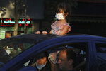 A girl wearing a protective face mask to help prevent the spread of the coronavirus looks through the sunroof of her family car on a street in central Tehran, Iran, Sunday, Aug. 8, 2021. Iranians are suffering through yet another surge in the coronavirus pandemic — their country's worst yet — and anger is growing at images of vaccinated Westerners without face masks on the internet or on TV while they remain unable to get the shots. (AP Photo/Vahid Salemi)