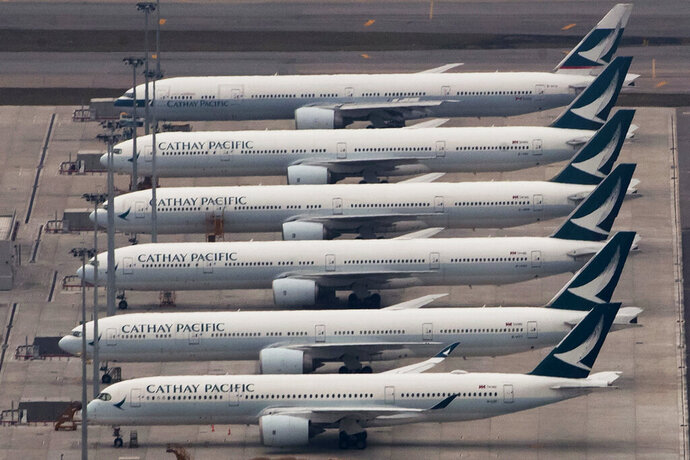FILE - In this March 6, 2020, file photo, Cathay Pacific Airways aircrafts line up on the tarmac at the Hong Kong International Airport. Hong Kong airline Cathay Pacific Airways on Wednesday, Oct. 21, 2020, said it would cut 8,500 jobs and shut down its regional airline unit in a corporate restructuring, as it grapples with the plunge in air travel due to the pandemic. (AP Photo/Kin Cheung)