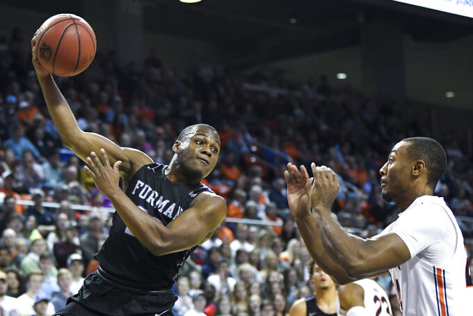 Furman guard Jordan Lyons (23) passes the ball over Auburn forward Anfernee McLemore (24) during the first half of an NCAA college basketball game Thursday, Dec. 5, 2019, in Auburn, Ala. (AP Photo/Julie Bennett)