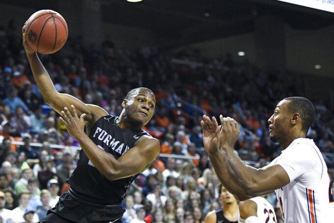 Furman guard Jordan Lyons (23) passes the ball over Auburn forward Anfernee McLemore (24) during the first half of an NCAA college basketball game Thursday, Dec. 5, 2019, in Auburn, Ala. (AP Photo/Julie Bennett)