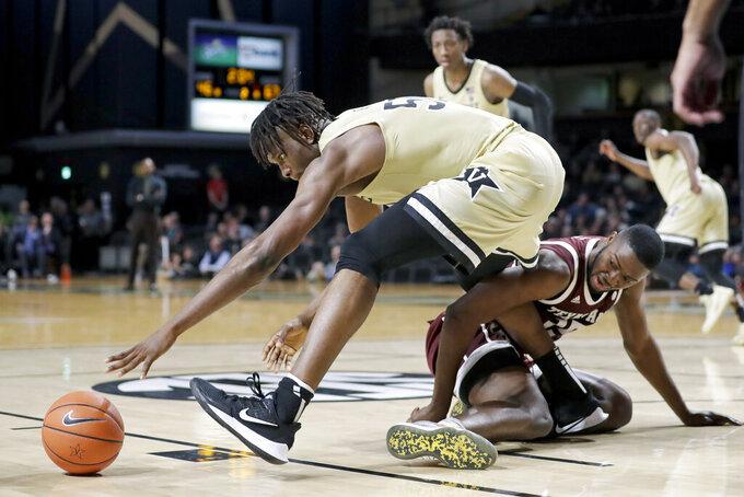 Vanderbilt forward Ejike Obinna, left, reaches for the ball over Texas A&M forward Jonathan Aku in the second half of an NCAA college basketball game Saturday, Jan. 11, 2020, in Nashville, Tenn. Texas A&M won 69-50. (AP Photo/Mark Humphrey)