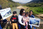 A Lebanese family holds placards during a protest against the Bisri dam project, in the Bisri Valley, 58 kilometers (36 miles) southeast of Beirut, Lebanon, Sunday, March. 10, 2019. Its expansive lands of pine, citrus trees and ancient ruins are about to turn into a controversial mega dam funded by the World Bank. For years now, activists and locals have voiced their opposition to what they describe as not only