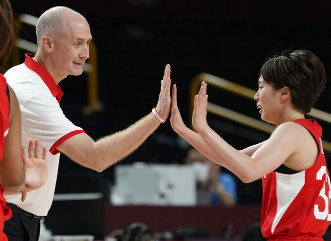 Japan's head coach Thomas Wayne Hovasse, left, high five with Japan's Saori Miyazaki (32) during women's basketball preliminary round game against the United States of America at the 2020 Summer Olympics, Friday, July 30, 2021, in Saitama, Japan. (AP Photo/Eric Gay)