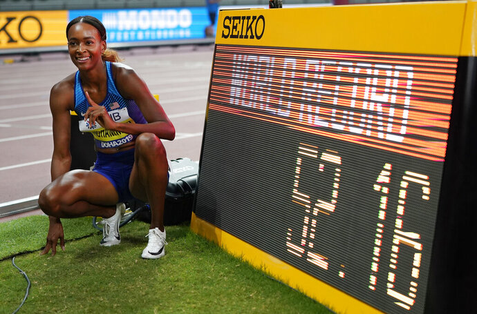 Dalilah Muhammad, of the United States, poses for a photo with the clock after winning the women's 400 meter hurdles final, setting a new world record at the World Athletics Championships in Doha, Qatar, Friday, Oct. 4, 2019. (AP Photo/David J. Phillip)