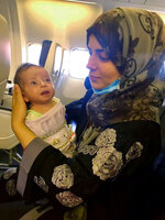 In this photo provided to The Associated Press, Storai Amini and her two-month-old daughter, Amina, are seen on Sunday, Sept. 19, 2021, on a flight from Mazar-e-Sharif, Afghanistan, to Lisbon, Portugal. Late Sunday night, almost three weeks after the American withdrawal from Afghanistan, members of the Afghanistan national girls soccer team and their families landed in Lisbon after an international coalition came to their rescue. (AP Photo)