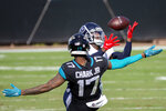 Tennessee Titans cornerback Malcolm Butler, right, intercepts a pass intended for Jacksonville Jaguars wide receiver DJ Chark Jr. (17) during the second half of an NFL football game, Sunday, Dec. 13, 2020, in Jacksonville, Fla. (AP Photo/Stephen B. Morton)