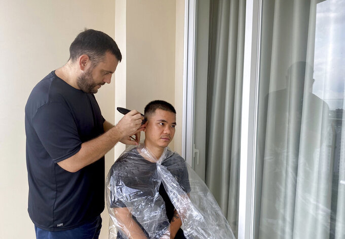 AP journalist Hau Dinh, right, gets a haircut from his partner Mathieu Le Besq during a virus lockdown in Vung Tau, Vietnam on Sept. 13, 2021. Dinh set off from Hanoi for the seaside resort for a long weekend in mid-July. The trip came just as the delta variant began sweeping through Vietnam, sparking harsh lockdown measures that left him trapped away from home. Nine weeks later, he's still there. (AP Photo/Hau Dinh)