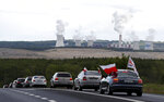 Cars drive slowly to block a border between Czech Republic and Poland near the Turow mine near Bogatynia, Poland, Tuesday, May 25, 2021. People in their cars protested against the decision of the European Union's top court on Friday, that ordered Poland to immediately stop extracting brown coal at the Turow mine near the border with the Czech Republic and Germany. (AP Photo/Petr David Josek)