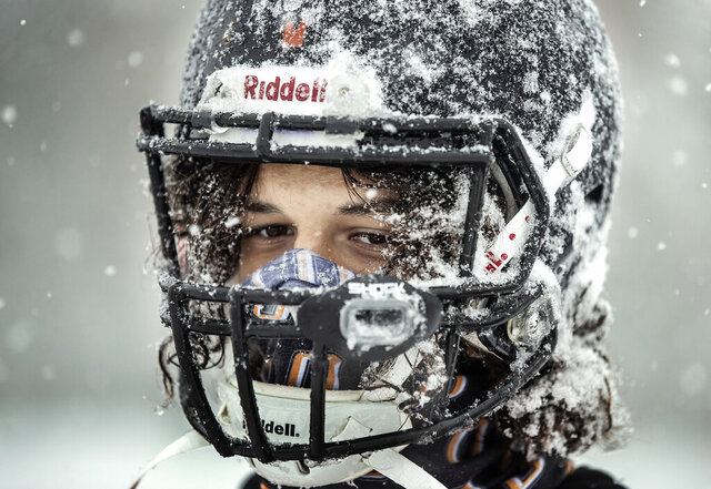 Milton DeJesus and members of the Osseo football team practiced outside in the heavy snow in preparation for their Friday night game against Totino-Grace, Tuesday, Oct. 20, 2020, in Maple Grove, Minn. (Jerry Holt/Star Tribune via AP)